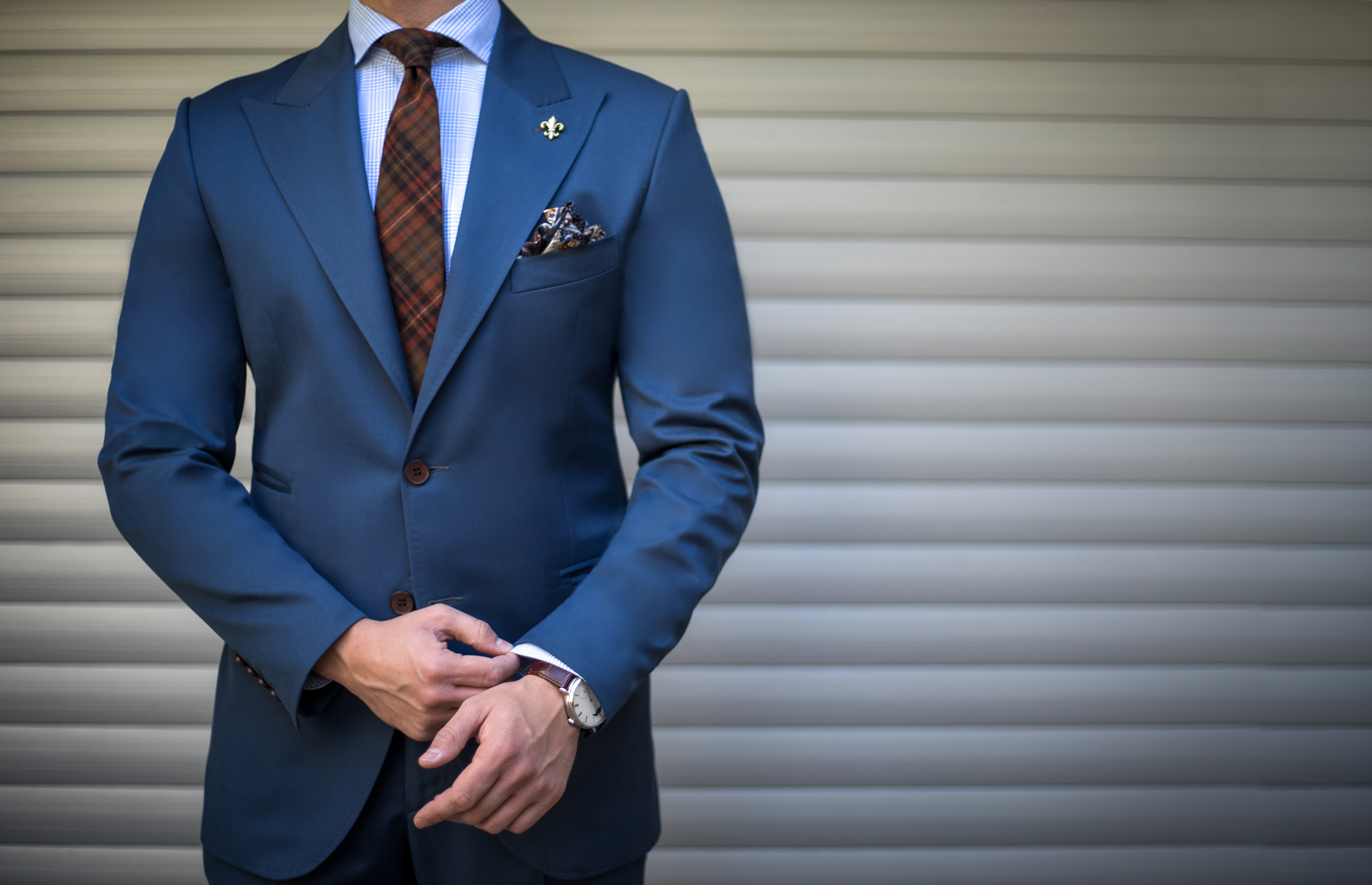 Male model in tailored suit posing outdoors and fixing his cufflinks